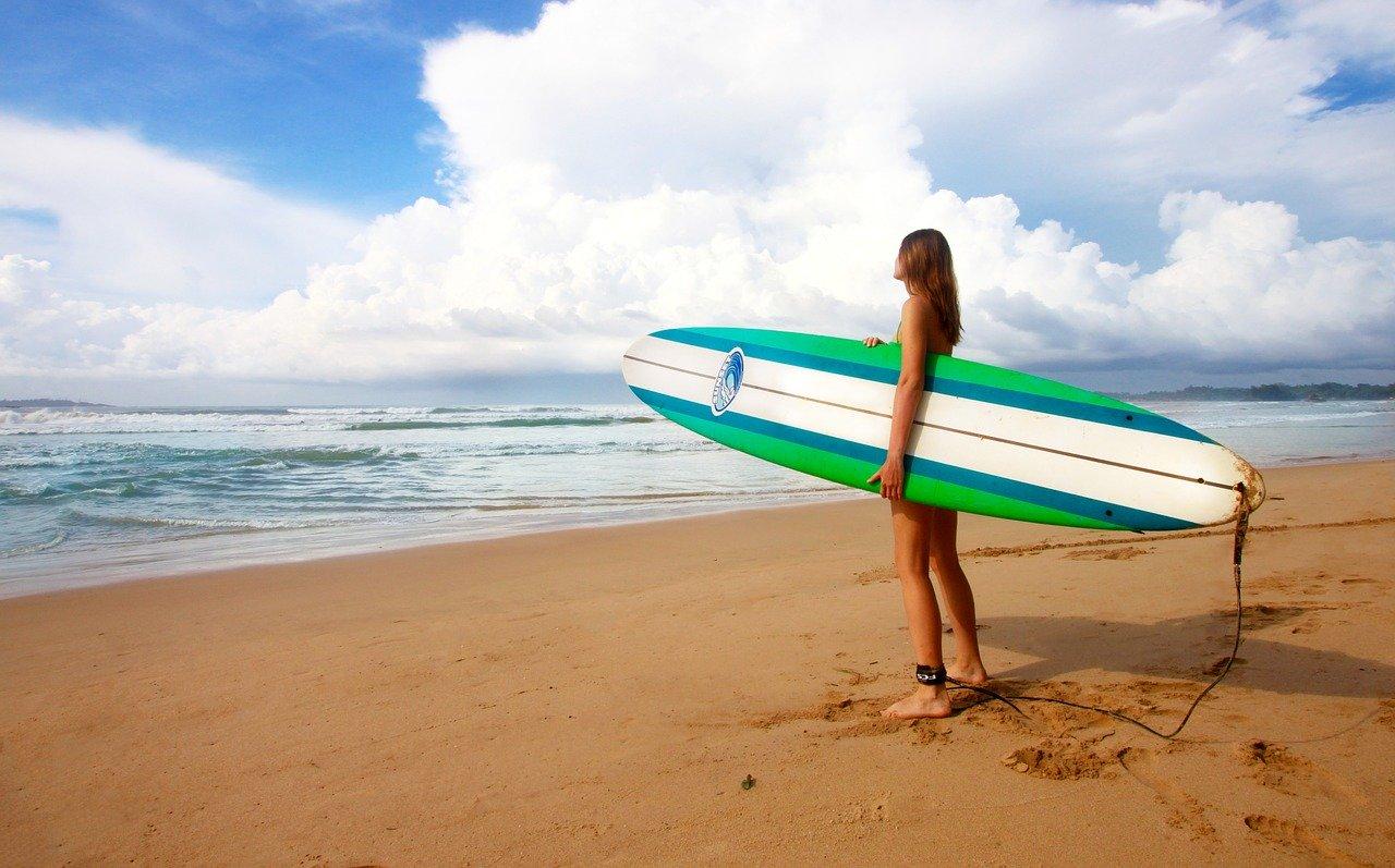 ロングボードを持つ女性サーファー
